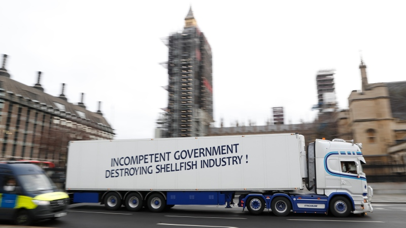 """A shellfish export truck with a protest sign written across the trailer 'Incompetent Government Destroying Shellfish Industry"""" drives past the Palace of Westminster in London, Monday, Jan. 18, 2021, during a demonstration by British Shellfish exporters to protest Brexit-related red tape they claim is suffocating their business. (AP Photo/Alastair Grant)"""