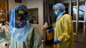 Health-care workers care for a COVID-19 patient in the ICU who is intubated and on a ventilator at the Humber River Hospital during the COVID-19 pandemic in Toronto on Wednesday, December 9, 2020. THE CANADIAN PRESS/Nathan Denette