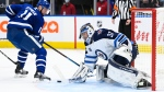 Winnipeg Jets goaltender Connor Hellebuyck (37) makes a save against Toronto Maple Leafs left wing Zach Hyman (11) during third period NHL hockey action in Toronto on Monday, January 18, 2021. THE CANADIAN PRESS/Nathan Denette