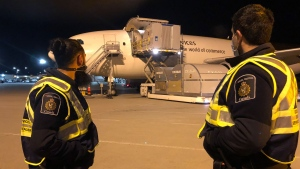 Canadian Border Services Agency officers watch as shipments of initial doses of COVID-19 vaccines arrive in Montreal on Sunday, December 13, 2020. THE CANADIAN PRESS/HO-Canada Border Services Agency