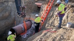 In this April 13, 2020, photo provided by TC Energy, construction contractors for TC Energy are seen installing a section of the Keystone XL crude oil pipeline at the U.S.-Canada border north of Glasgow, Mont.(TC Energy via AP)