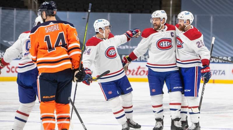 Edmonton Oilers' Devin Shore (14) skates past as Montreal Canadiens' Nick Suzuki (14), Shea Weber (6) and Jeff Petry (26) celebrate a goal during first period NHL action in Edmonton on Saturday, January 16, 2021. (THE CANADIAN PRESS/Jason Franson)