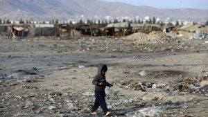 An internally displaced boy walks outside his temporary home in the city of Kabul, Afghanistan, Monday, Jan. 18, 2021. (AP Photo/Rahmat Gul)