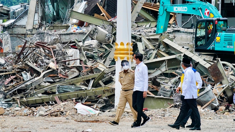 In this photo released by the Indonesian Presidential Palace, President Joko Widodo, centre, talks to an official as he inspects an earthquake-damaged government building, in Mamuju, West Sulawesi, Indonesia, Tuesday, Jan. 19, 2021. (Indonesian Presidential Palace via AP)