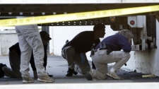 Members of the FBI investigate under a semi trailer outside a warehouse in Dearborn, Mich., Wednesday, Oct. 28, 2009. (AP Photo/Paul Sancya)