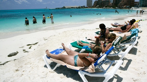Tourists enjoy the beach at the resort city of Cancun, Mexico. (AP / Israel Leal)