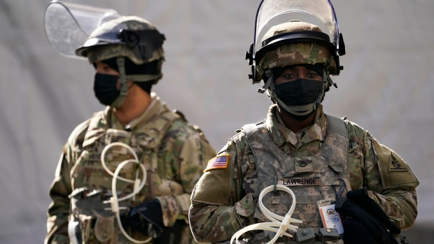 National Guard stand outside a checkpoint on as security is heightened ahead of President-elect Joe Biden's inauguration ceremony, Tuesday, Jan. 19, 2021, in Washington. (AP Photo/John Minchillo)