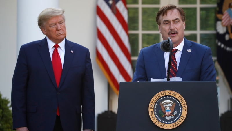 In this March 30, 2020 file photo, My Pillow CEO Mike Lindell speaks as U.S. President Donald Trump listens during a briefing about the coronavirus in the Rose Garden of the White House, in Washington. (AP Photo/Alex Brandon, File)