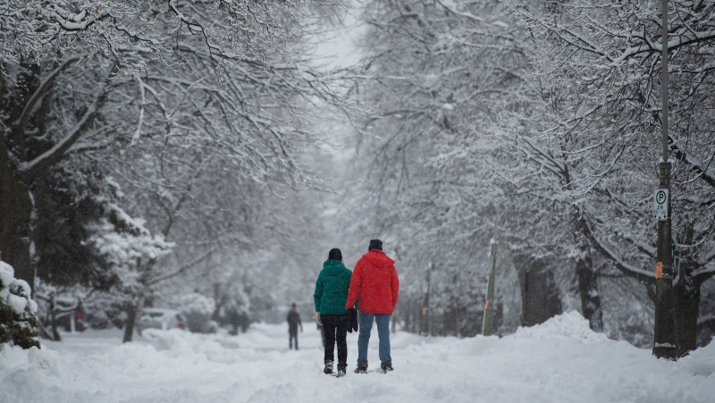People walk on the snow-covered street in Ottawa's Glebe neighbourhood during a major snowstorm on Saturday, Jan. 16, 2021. A snowfall warning is in effect with Environment Canada predicting between 15 to 30 cm of snow by tonight. (Justin Tang/THE CANADIAN PRESS)