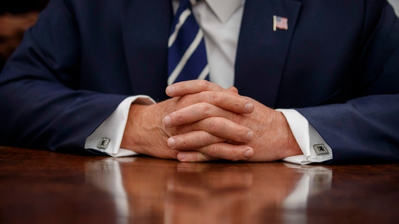 The hands of U.S. President Donald Trump are folded on the Resolute desk during a photo opportunity in the Oval Office of the White House, Friday, July 19, 2019, in Washington. (AP Photo/Alex Brandon)