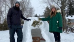 Marco Santangelo and Moca Ford pose with their igloo in Carleton Place, Ont. (Dylan Dyson / CTV News Ottawa)
