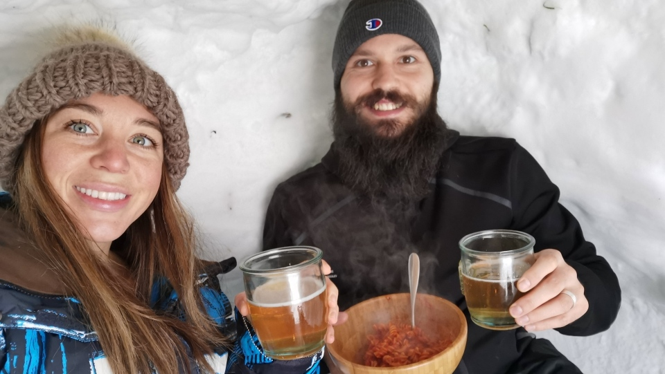 Moca Ford and Marco Santangelo enjoy pasta and beer in their igloo in Carleton Place, Ont. (Photo submitted by Moca Ford)