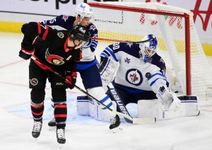 Ottawa Senators left wing Brady Tkachuk (7) attempts to chip a puck past Winnipeg Jets goaltender Laurent Brossoit (30) as Jets centre Paul Stastny (25) defends during first period NHL action in Ottawa on Tuesday, Jan. 19, 2021. THE CANADIAN PRESS/Sean Kilpatrick