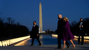 With the Washington Monument in the background, President-elect Joe Biden walks with his wife Jill Biden as lights are placed around the Lincoln Memorial Reflecting Pool during a COVID-19 memorial Tuesday, Jan. 19, 2021, in Washington. (AP Photo/Evan Vucci)