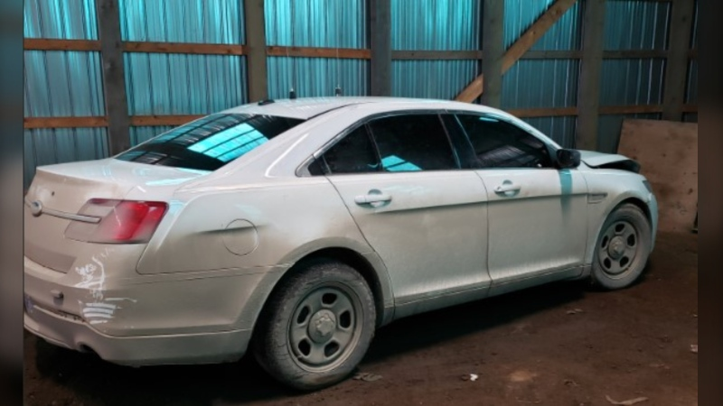 Police describe the seized vehicle as a white 2013 Ford Taurus with reflective striping along both sides, with a microphone attached to the dashboard, LED lights, and a black push bar mounted on the grill. (Photo courtesy: RCMP)