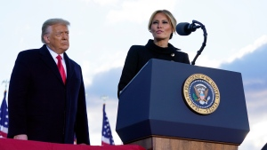 President Donald Trump listens as First Lady Melania Trump speaks before boarding Air Force One at Andrews Air Force Base, Md., Wednesday, Jan. 20, 2021.(AP Photo/Manuel Balce Ceneta)