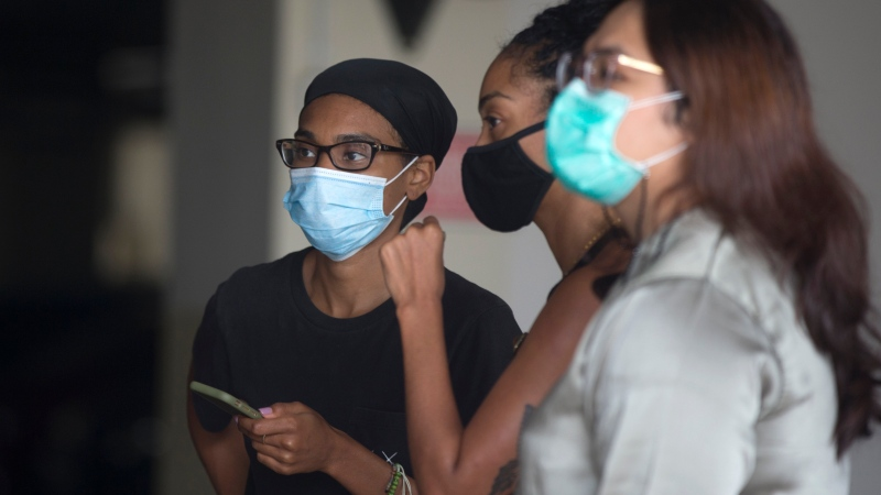 American graphic designer Kristen Antoinette Gray, left, stands with her partner Saundra Michelle Alexander, center, for a test for the coronavirus at a hospital in Denpasar, Bali, Indonesia on Wednesday, Jan. 20, 2021. (AP Photo/Firdia Lisnawati)