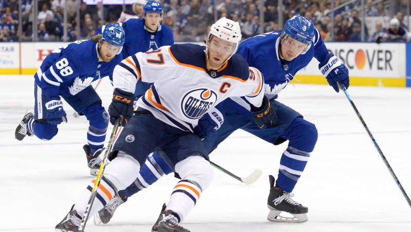Toronto Maple Leafs defenceman Justin Holl (3) picks up a penalty on Edmonton Oilers centre Connor McDavid (97) during third period NHL hockey action in Toronto on Monday Jan. 6, 2020. THE CANADIAN PRESS/Nathan Denette