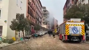 In this image made from video provided by Emergencias Madrid, firefighters attend the scene after an explosion in Madrid, Wednesday, Jan. 20, 2021. (Emergencias Madrid via AP)