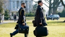 A U.S. military aide, left, carries the 'president's emergency satchel,' also known as 'the football,' with the nuclear launch codes, as U.S. President Donald Trump walks to board Marine One on the South Lawn of the White House, Tuesday, Jan. 12, 2021, in Washington. (AP Photo/Gerald Herbert )