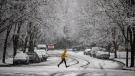 Heavy snow falls as a man sprints across a road in Burnaby, B.C., on Monday, Dec. 21, 2020. (Darryl Dyck / THE CANADIAN PRESS)