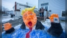 Sixteen-year-old Ashton Keating, left, and his father James Keating pose for a photo with a snow sculpture they created on their front lawn in St. John's, Wednesday, Jan. 20, 2021. The sculpture depicts former US President Donald Trump descending into the water. THE CANADIAN PRESS/Paul Daly