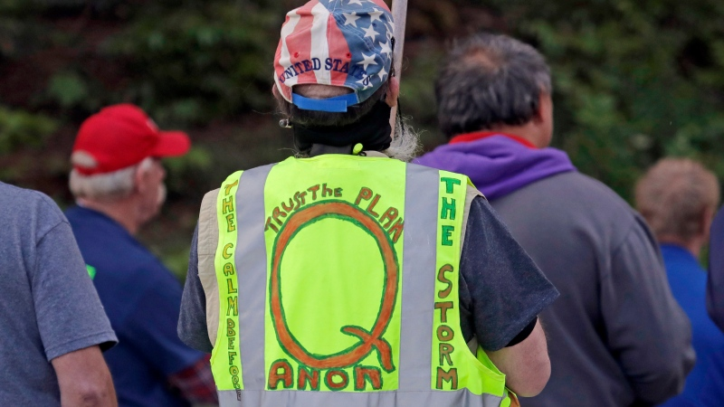 In this May 14, 2020, file photo, a person wears a vest supporting QAnon at a protest rally in Olympia, Wash., against Gov. Jay Inslee and Washington state stay-at-home orders made in efforts to prevent the spread of the coronavirus. (AP Photo/Ted S. Warren, File)