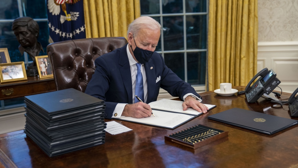 U.S. President Joe Biden signs executive orders in the Oval Office of the White House in Washington, D.C., U.S., on Wednesday, Jan. 20, 2021. Joe Biden began his presidency with a soaring appeal to end Americas