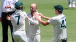 Australia's Nathan Lyon, centre, is congratulated by teammates Tim Paine, left, and Cameron Green after taking the wicket of India's Shubman Gill for 91 runs during play on the final day of the fourth cricket test between India and Australia at the Gabba, Brisbane, Australia, Tuesday, Jan. 19, 2021. (AP Photo/Tertius Pickard)