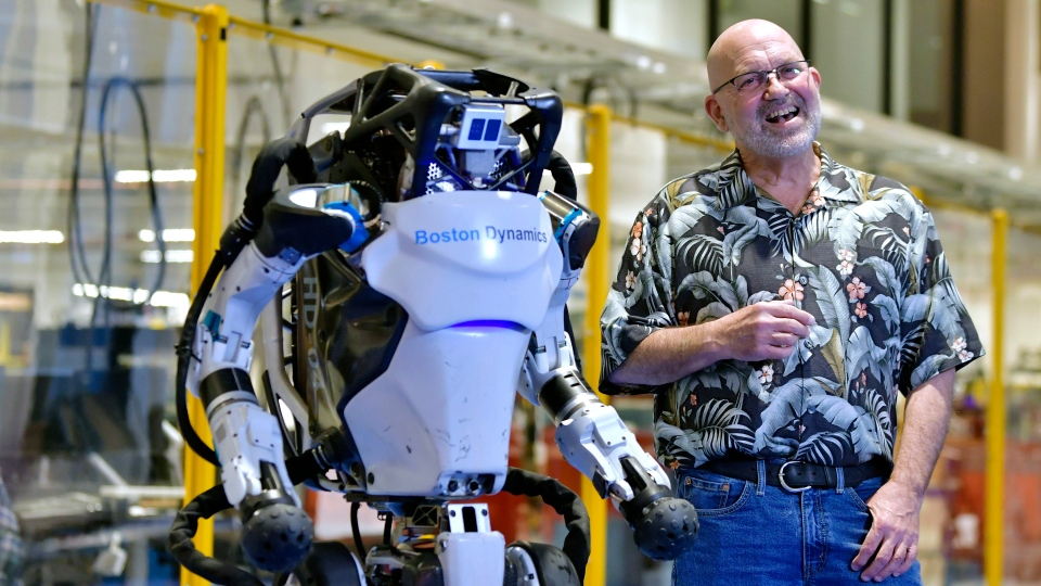 Marc Raibert, founder and chair of Boston Dynamics stands beside one of the company's Atlas robots during an interview and demonstration, Wednesday, Jan. 13, 2021, at their facilities in Waltham, Mass. (AP Photo/Josh Reynolds)