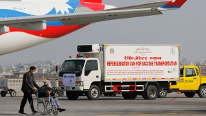 A van stands parked waiting to transport AstraZeneca/Oxford University vaccines, manufactured under license by Serum Institute of India, at Tribhuwan International Airport in Kathmandu, Nepal, Thursday, Jan. 21, 2021. (AP Photo/Niranjan Shrestha)