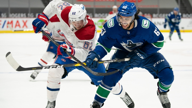 Vancouver Canucks defenceman Jalen Chatfield (63) fights for control of the puck with Montreal Canadiens left wing Artturi Lehkonen (62) during third period NHL action in Vancouver, Wednesday, January 20, 2021. THE CANADIAN PRESS/Jonathan Hayward