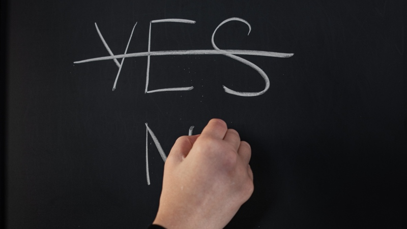 A person is seen writing 'NO' on a chalkboard. (Pexels)
