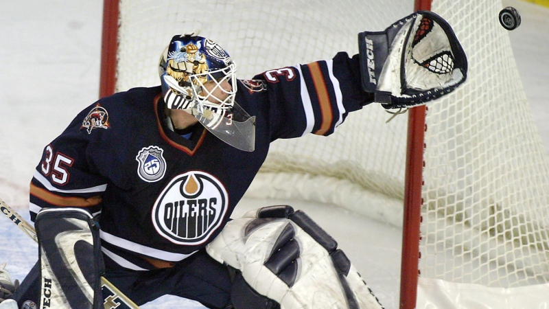Edmonton Oilers goalie Tommy Salo reaches for a shot against the Florida Panthers during the first period of NHL play in Edmonton on Jan. 13, 2004 (CP Photo/John Ulan)