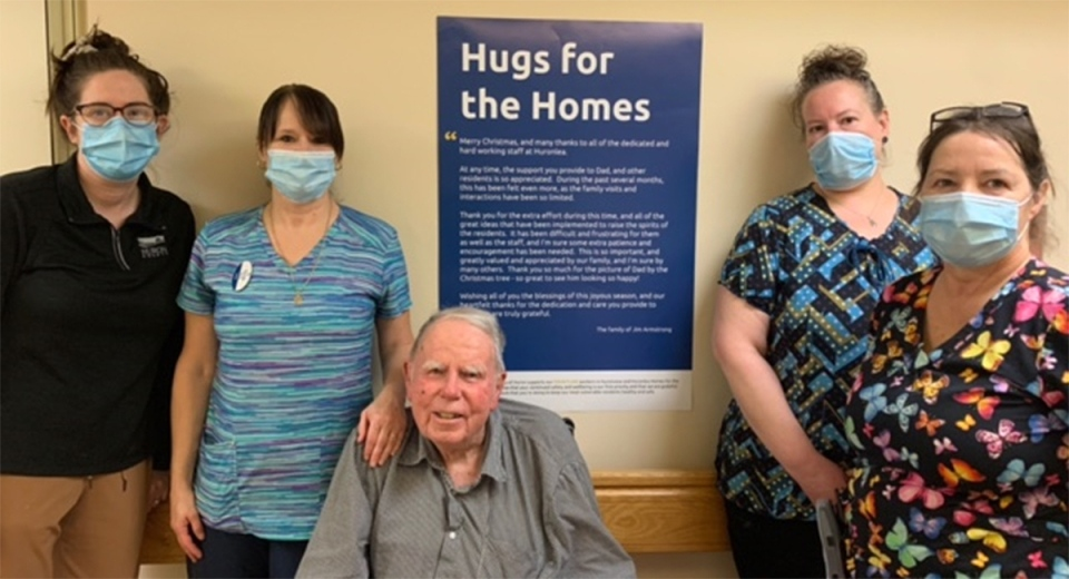 Staff and a resident at a Huron County, Ont. long-term care home stand in front an inspirational quote from Hugs for the Homes.