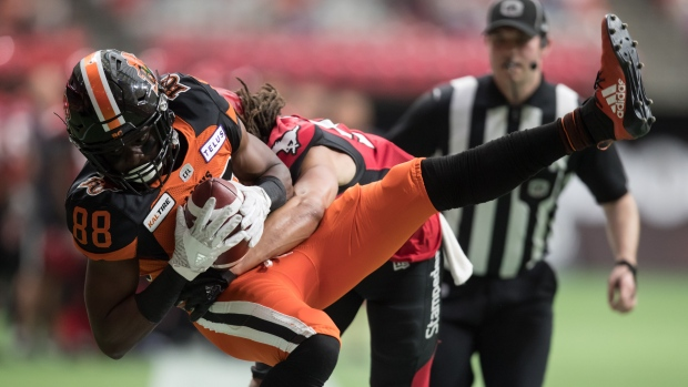 B.C. Lions' Shaq Johnson, front, is hit by Calgary Stampeders' Jamari Gilbert after making a reception during the first half of a pre-season CFL football game in Vancouver, on June 7, 2019. THE CANADIAN PRESS/Darryl Dyck