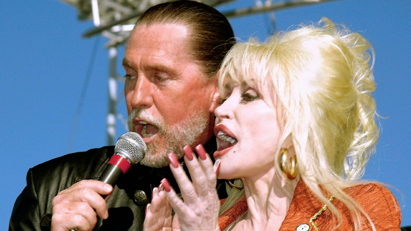 Dolly Parton shares the microphone with her brother Randy Parton during a celebration marking the groundbreaking for the Carolina Crossroads Music & Entertainment Center in Roanoke Rapids, N.C. on Nov. 11, 2005. Parton said her brother and singing partner Randy Parton has died of cancer. She said in a statement released Thursday that her brother sang, played guitar and bass in her band, as well hosting his own show at her theme park, Dollywood, in East Tennessee. He was 67. (Todd Wetherington/The Daily Herald via AP)