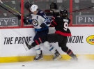 Winnipeg Jets' Mark Scheifele collides with Ottawa Senators' Josh Norris along the boards during second period NHL action Thursday, January 21, 2021 in Ottawa. THE CANADIAN PRESS/Adrian Wyld
