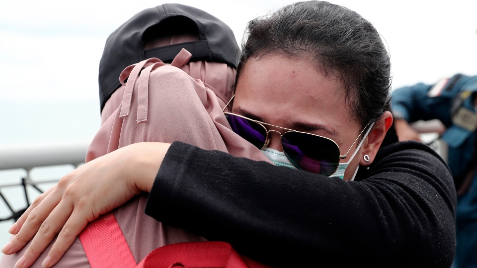 Relatives of the victims of Sriwijaya Air flight SJ-182 comfort each other during a memorial ceremony held on the deck of Indonesian Navy Ship KRI Semarang that sails in the Java Sea where the plane crashed on Jan. 9 killing all of its passengers, near Jakarta in Indonesia, Friday, Jan. 22, 2021. (AP Photo/Tatan Syuflana)