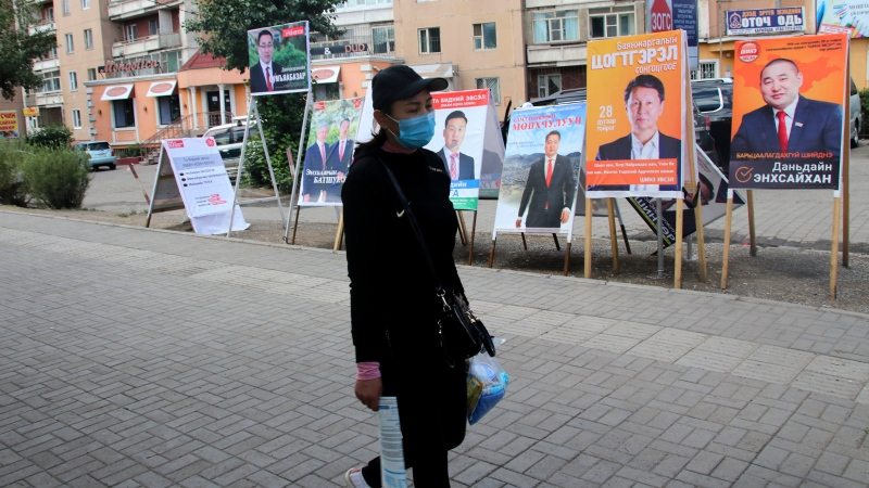 A resident carries groceries past posters and stands of various political party and independent candidates in the Songinokhairkhan district on the outskirts of Ulaanbaatar, Mongolia, Monday, June 22, 2020. (AP Photo/Ganbat Namjilsangarav)