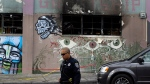 In this Dec. 9, 2016 file photo, an Oakland police officer guards the area in front of the art collective warehouse known as the Ghost Ship in the aftermath of a fire in Oakland, Calif. (AP Photo/Ben Margot, File)