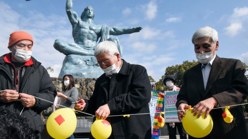 Participants deflate balloons in hope of neutralizing and demolishing nuclear warheads, during a memorial gathering at Peace Park in Nagasaki, southern Japan Friday, Jan. 22, 2021. (Kyodo News via AP)