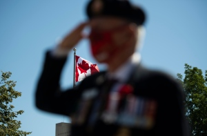 The Canadian flag is seen as a veteran salutes during a ceremony marking the 75th anniversary of V-J Day and the end of the Second World War, in Ottawa, on Saturday, Aug. 15, 2020. (THE CANADIAN PRESS/Justin Tang)