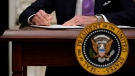 U.S. President Joe Biden signs executive orders after speaking about the coronavirus in the State Dinning Room of the White House, Thursday, Jan. 21, 2021, in Washington. (AP Photo/Alex Brandon)