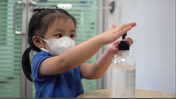 Young kid puts on hand sanitizer