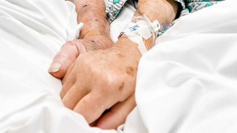 Photo taken at the hospital of Dick and Shirley holding hands before they died. (Courtesy Debbie Howell)