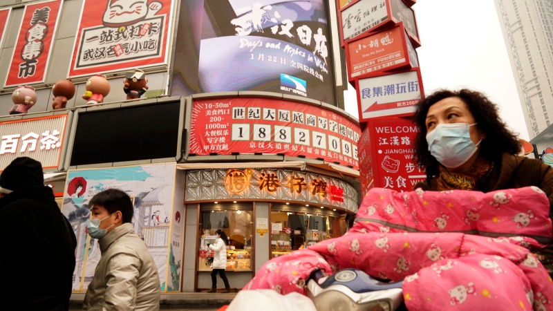 "Residents wearing masks past by a screen showing a trailer for the film ""Days and Nights in Wuhan"" outside a mall in Wuhan in central China's Hubei province on Friday, Jan. 22, 2021. China is rolling out the state-backed film praising Wuhan ahead of the anniversary of the 76-day lockdown in the central Chinese city where the coronavirus was first detected. (AP Photo/Ng Han Guan)"