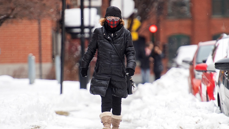 A woman wears a face mask as she walks along a street in Montreal, Sunday, January 17, 2021, as the COVID-19 pandemic continues in Canada and around the world. The Quebec government has imposed a lockdown and a curfew to help curb the spread of COVID-19. The curfew begins at 8 p.m until 5 a.m and lasting until February 8. THE CANADIAN PRESS/Graham Hughes