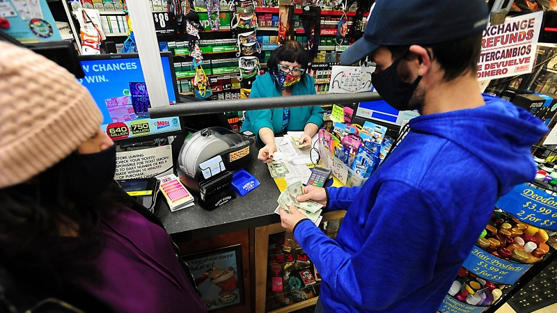 Michael and Amanda Lazovich of Plain, Pa., purchase Powerball and Mega Millions lottery tickets at the Anthracite Newsstand on Public Square in Wilkes-Barre, Pa., Thursday, Jan. 14, 2021.