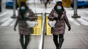A pedestrian wearing a mask walks through an empty downtown Calgary, Alta., Wednesday, Dec. 9, 2020, after new provincial restrictions were announced amid a worldwide COVID-19 pandemic. THE CANADIAN PRESS/Jeff McIntosh